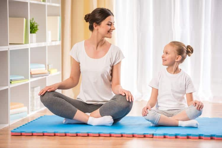 Mother and daughter sitting on yoga mat.
